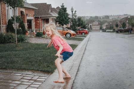 Cute adorable girl running splashing under rain on street road. Child having fun during rain shower storm. Seasonal summer outdoor activity for kids. Freedom and happy childhood lifestyle.