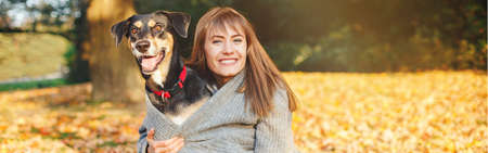 Happy young Caucasian woman hugging dog. Owner walking with pet on autumn fall day. Best friends having fun outdoor. Friendship of human with domestic animal. Web banner header. Stock Photo