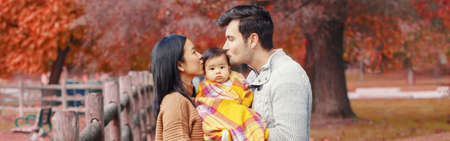 Asian Chinese mother and Caucasian father dad holding kissing baby girl wrapped in blanket. Family in autumn fall park outdoor. Seasonal holiday Thanksgiving. Web banner header for website. Stock Photo