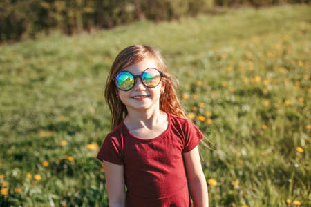 Happy smiling young Caucasian girl in funny sunglasses posing outdoor. Cute adorable kid child having fun outside. Happy childhood lifestyle. Sincere positive emotion. Banque d'images