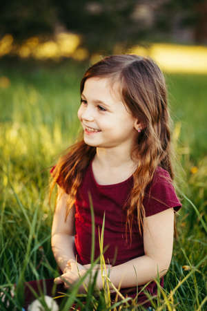 Closeup portrait of funny smiling laughing young Caucasian girl outdoor. Cute adorable kid child having fun outside. Happy childhood lifestyle. Sincere positive emotion.