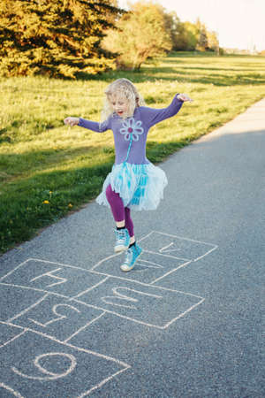 Cute adorable little young chld girl playing hopscotch outdoor. Funny activity game for kids on playground outside. Summer backyard street sport for children. Happy childhood lifestyle.