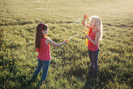 Catch a bubble. Girls friends blowing soap bubbles in park on summer day. Kids having fun outdoor. Authentic happy childhood magic moment. Lifestyle seasonal activity for children.