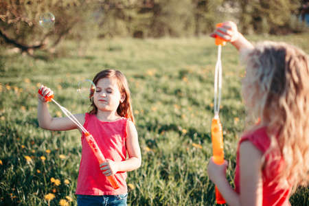 Funny hilarious moment. Girls friends blowing soap bubbles in park on summer day. Kids having fun outdoor. Authentic happy childhood lifestyle. Seasonal activity for children.