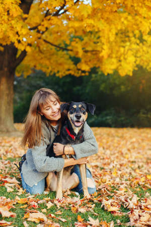 Happy young Caucasian woman sitting on ground hugging dog. Owner walking with pet on autumn fall day. Best friends having fun outdoor. Friendship of human with domestic animal. Banque d'images