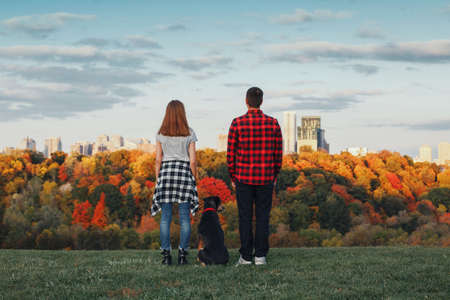 Man, woman and dog pet standing on hill in front of city urban town dreaming of future or remembering past time. View from back. Family with domestic animal. Concept of dreams or travel. Banque d'images