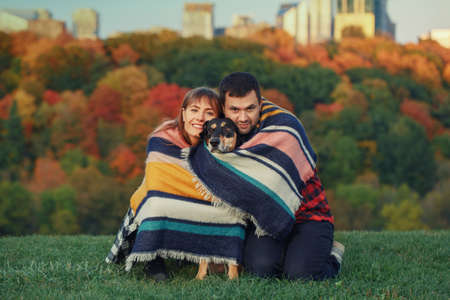 Beautiful young couple with dog in park. Man and woman hugging playing with their domestic animal pet outdoor on autumn fall day. Family authentic lifestyle activity. Love and friendship.