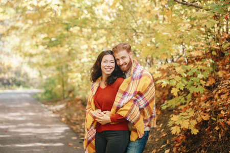 Beautiful couple man woman in love. Boyfriend and girlfriend wrapped in yellow blanket plaid hugging together in park on autumn fall day. Tenderness and happiness. Authentic real people.