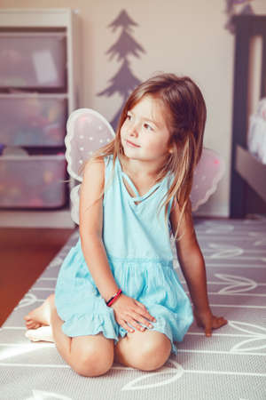 Cute adorable pretty dressed preschool girl playing fairy princess at home. Child creativity imagination and fantasy dreams concept. Beautiful Caucasian kid in blue dress pretending a fairy or elf. Banque d'images