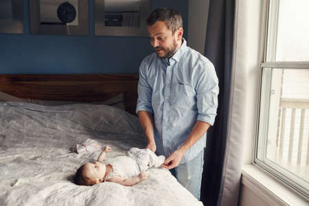 Middle age Caucasian father changing diaper clothes for newborn baby daughter son. Man parent taking care of child at home. Authentic lifestyle candid moment. Single dad family day life.
