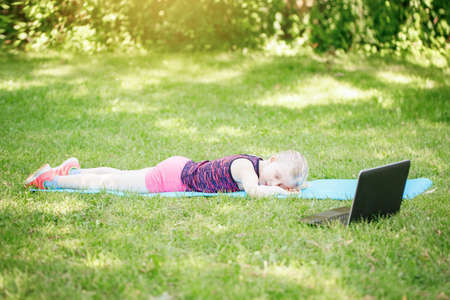 Bored tired girl child sleeping while doing sport workout outdoor online. Video yoga class on Internet. Funny sleeping kid training at home with laptop. New normal. Social distance at coronavirus.