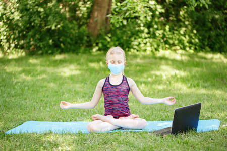 Caucasian girl child in face mask doing sport workout outdoor online. Video yoga on Internet. Kid learning training on backyard at home with laptop. New normal. Social distance at coronavirus. Banque d'images
