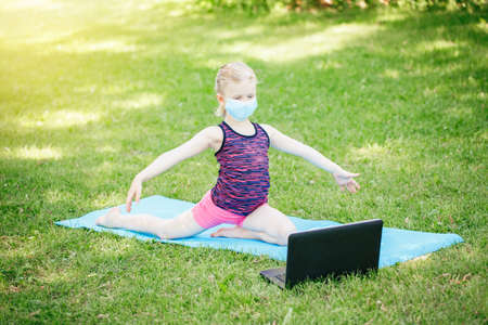 Caucasian girl child in face mask doing sport workout outdoor online. Video yoga stretching on Internet. Kid learning training on backyard with laptop. New normal. Social distance at coronavirus.