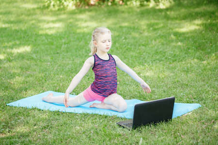 Caucasian girl child doing sport workout outdoor online. Video yoga stretching on Internet. Kid learning training on backyard at home with laptop. New normal. Social distance at coronavirus. Banque d'images