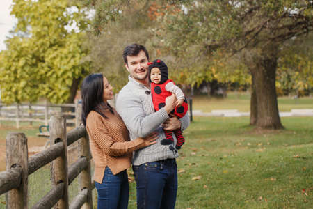 Happy smiling Asian Chinese mother and Caucasian father dad with baby girl in ladybug costume. Family in autumn fall park outdoor. Halloween or Thanksgiving holiday concept.
