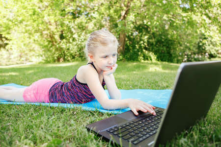 Caucasian girl child doing sport workout outdoor online. Video chat call with friends on Internet. Kid learning training on backyard with laptop. New normal. Social distance at coronavirus.