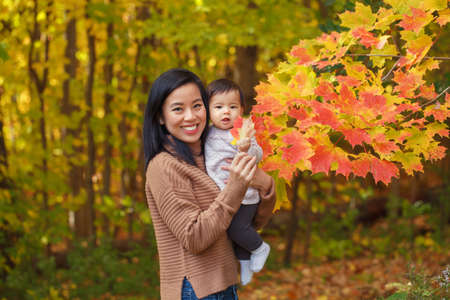 Asian Chinese mother holding cute adorable  baby girl on hands in autumn fall park. Outdoor seasonal nature with yellow red leaves trees. Halloween or Thanksgiving autumnal holidays.