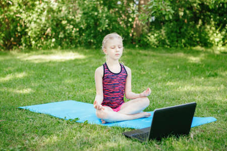 Caucasian girl child practicing yoga outdoor online. Video sport workout on Internet. Kid learning fitness training with laptop. New normal. Social distance at coronavirus. Stress relief concept.