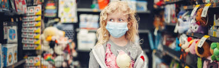 A new normal. Caucasian blonde girl child in sanitary face mask shopping at toy store. Safety, health protection during covid-19 quarantine. Web banner header for website.