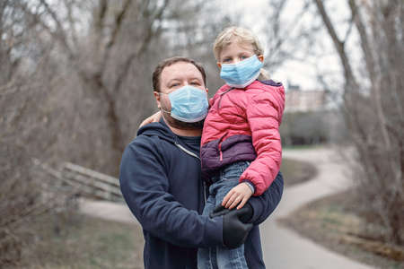 Caucasian father with child girl wearing sanitary face masks outdoor. Family dad and daughter protect themselves from dangerous spread of virus. Coronavirus COVID-19 quarantine. Imagens