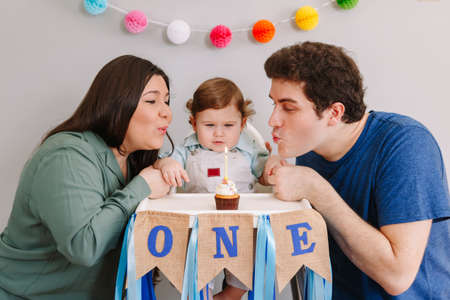 Caucasian family with baby boy celebrating his first birthday at home. Mother father dad with child kid toddler blowing candle on cupcake. Happy birthday and cake smash concept. Imagens