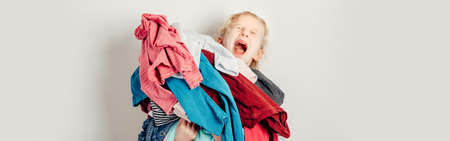 Mommy little helper. Adorable funny tired child arranging organazing clothing. Kid holding messy stack pile of clothes things. Home chores housework. Web banner header for website. Imagens