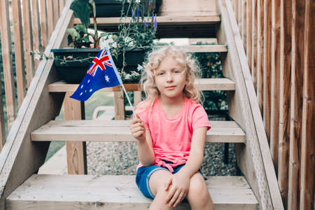 Adorable cute happy Caucasian girl holding Australian flag. Smiling child sitting on backyard at home and holding Australia flag. Kid citizen celebrating Australia Day holiday in January outdoor.