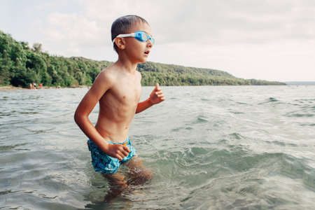 Caucasian boy swimming in lake river with underwater goggles. Child diving in water on beach. Authentic real lifestyle happy childhood. Summer fun outdoor aquatic recreational activity.