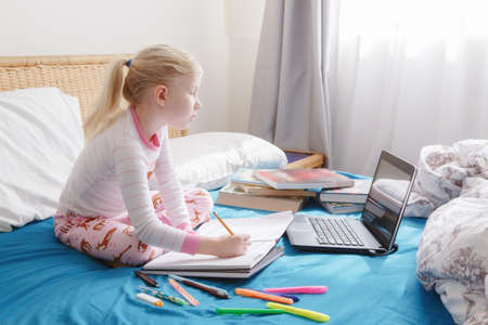 Caucasian girl child learning online on laptop Internet. Virtual class school on video call during self isolation quarantine at home. Distant remote education class. New normal and homeschooling.