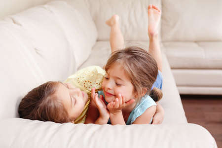 Two cute little Caucasian girls siblings playing at home. Adorable smiling children kids lying on couch together. Authentic candid lifestyle domestic life moment. Happy friends sisters relationship. Imagens