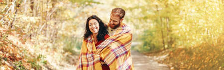 Beautiful couple man woman in love. Boyfriend and girlfriend wrapped in yellow blanket hugging together in park on autumn fall day. Authentic real people. Web banner header for website. Imagens