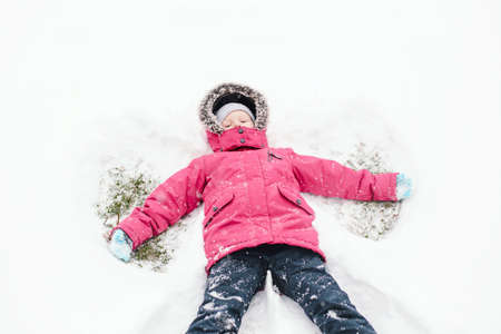 Cute adorable funny Caucasian girl child in warm clothes pink jacket making snow angel. Kid lying on ground during cold winter snowy day. Kids outdoor seasonal activity. View from top above.