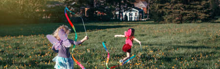 Children girls playing with ribbons in park. Kids running on meadow together. Outdoor summer backyard activity. Happy childhood candid authentic lifestyle. Web banner header for website. Imagens