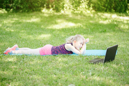 Bored tired girl child doing sport workout outdoor online. Video yoga class on Internet. Funny sleepy kid training at home backyard park with laptop. New normal. Social distance at coronavirus. Imagens