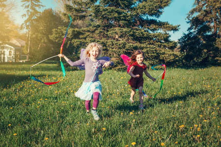 Happy children girls playing with ribbons in park. Cute adorable kids running on meadow playing together. Outdoor summer backyard activity for kids. Happy childhood candid authentic lifestyle.