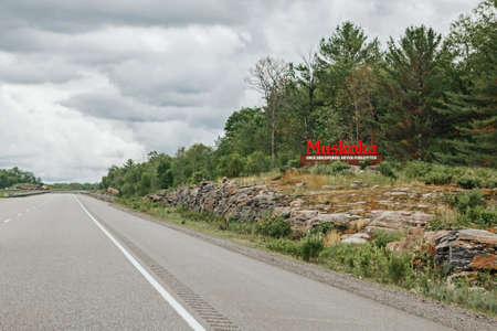 Canadian Ontario touristic destination place landmark. Red word sign Muskoka on empty road in Canada. Summer adventure trip on road. National place for vacation, travel and sightseeing outdoor.