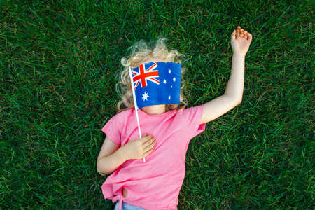 Adorable cute happy Caucasian girl holding Australian flag. Funny child kid covering her face with Australia flag. Little citizen celebrating Australia Day holiday in January outdoor.