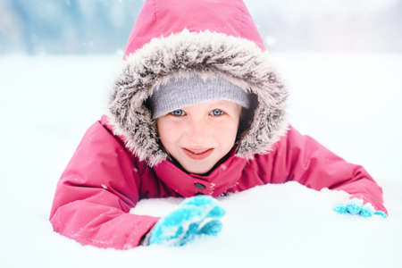 Cute Caucasian smiling excited girl child in pink jacket playing with snow. Kid lying on ground during cold winter snowy day at snowfall. Kids outdoor seasonal activity. Funny face. Imagens