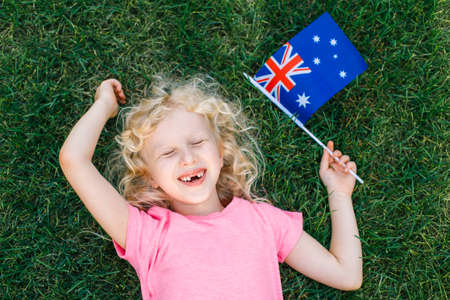 Adorable cute happy Caucasian girl holding Australian flag. Smiling laughing child lying on grass in park holding Australia flag. Kid citizen celebrating Australia Day holiday in January outdoor.