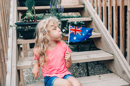 Adorable cute happy Caucasian girl holding blowing on Australian flag. Funny child sitting on backyard at home and holding Australia flag. Kid citizen celebrating Australia Day holiday.