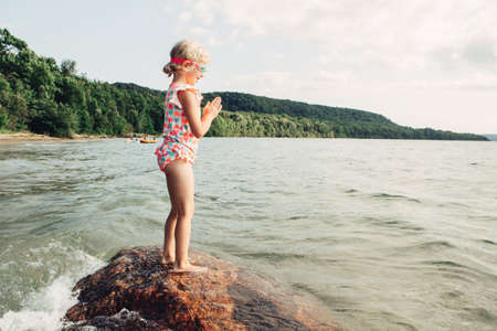 Cute funny Caucasian girl swimming in lake river with underwater goggles. Child diving in water. Authentic real lifestyle happy childhood. Summer fun outdoor aquatic recreational activity. Imagens
