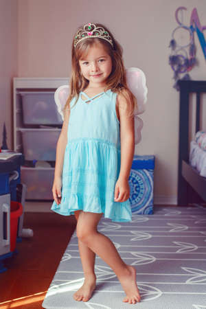 Cute adorable pretty dressed preschool girl playing fairy princess at home. Child creativity imagination and fantasy dreams concept. Beautiful Caucasian kid in crown pretending a fairy or elf.