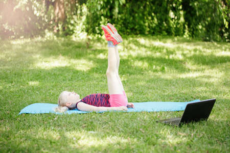 Caucasian girl child doing sport workout outdoor online. Video yoga stretching on Internet. Kid learning training on backyard at home with laptop. New normal. Social distance at coronavirus. Imagens