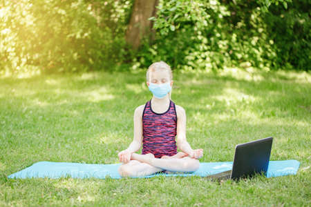 Caucasian girl child in face mask doing sport workout outdoor online. Video yoga on Internet. Kid learning training on backyard at home with laptop. New normal. Social distance at coronavirus. Imagens