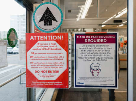 Toronto, Ontario, Canada - July 21, 2020: Warning notice on store shop door to wear protection face mask when entering. Precaution against coronavirus covid-19 spread. New normal rules.