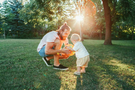 Young father playing ball with toddler baby boy outdoor. Parent spending time together with child son in park. Authentic lifestyle tender moment. Happy dad and active family life.