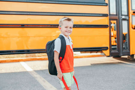 Happy smiling Caucasian boy elementary student with backpack near yellow bus on first September day. Education and back to school in autumn fall. Child kid on schoolyard outdoor. Standard-Bild