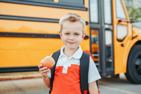 Caucasian boy student with backpack near yellow bus on first September day. Child kid eating apple fruit at school yard outdoor. Education and back to school in Autumn Fall. Stock Photo