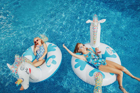 Cute adorable girls sisters friends with drinks lying on inflatable rings unicorns. Kids children siblings in sunglasses having fun in swimming pool. Summer outdoor water activity for kids.