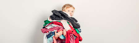 Mommy little helper. Adorable funny child arranging organazing clothing. Kid holding messy stack pile of clothes things. Home chores housework. Web banner header.
